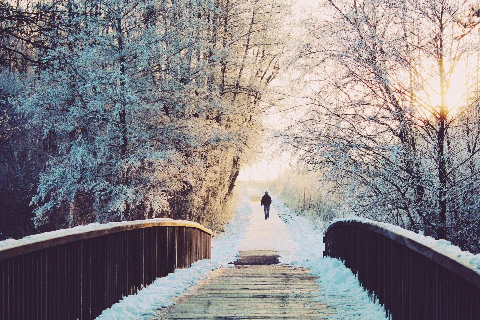 Man som går över snöig bro