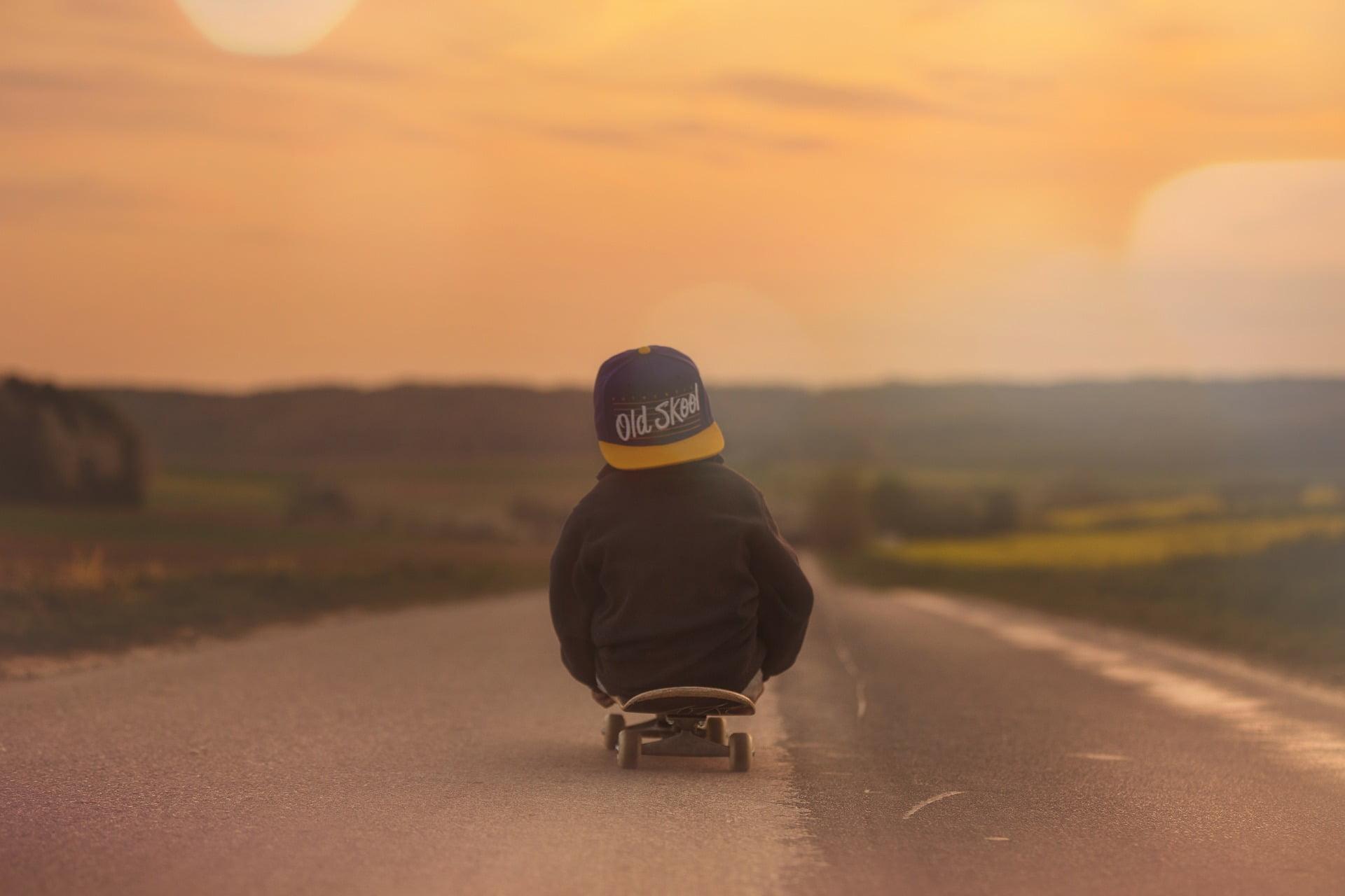 Pojke som sitter på skateboard i solnedgång