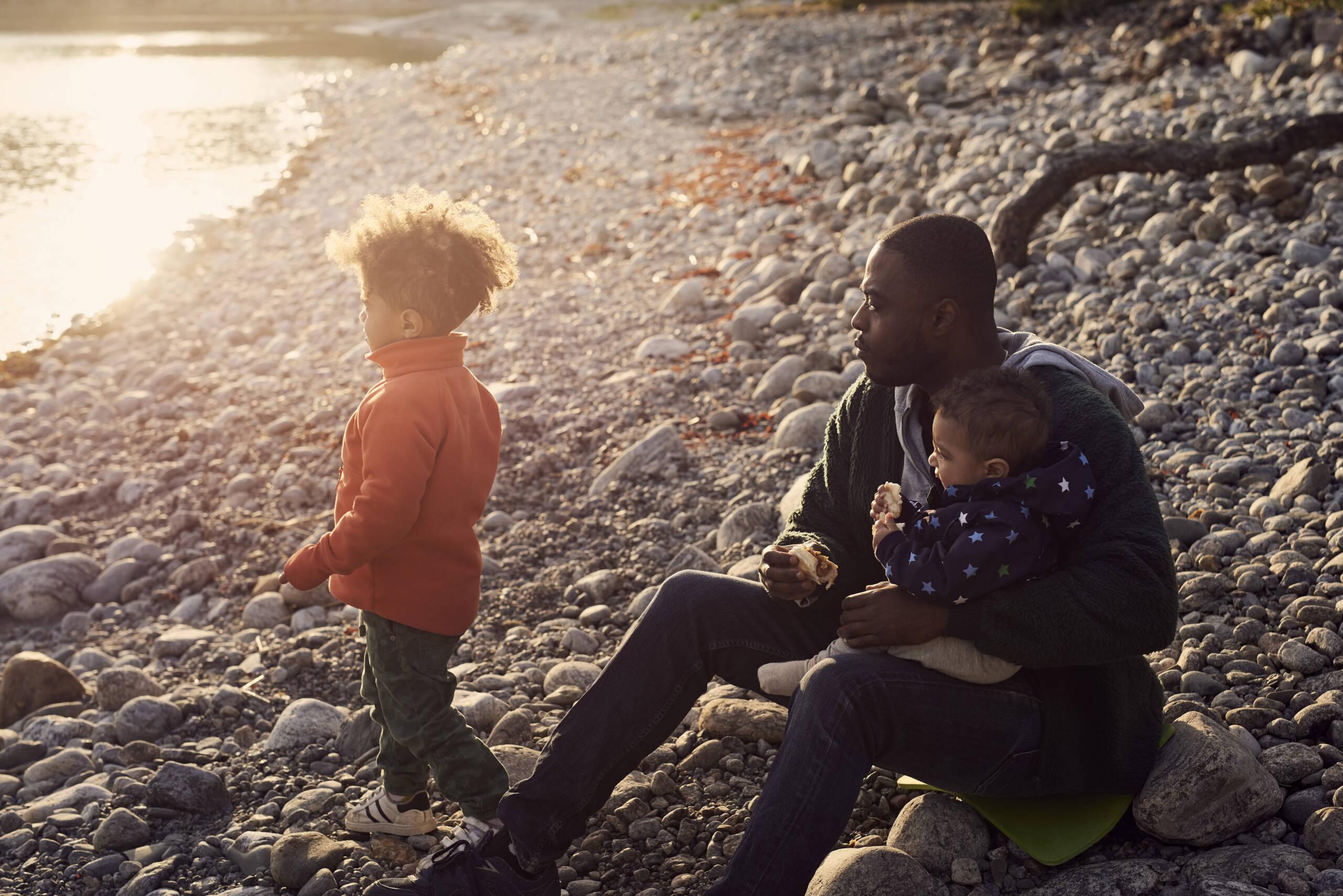 Pappa sitter på strand med bebis i knät och son bredvid